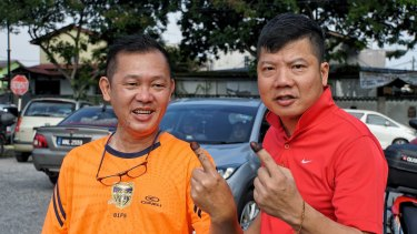 Alex Lum, left, and KC Yum holding up their inked fingers after voting in Selangor, Malaysia.