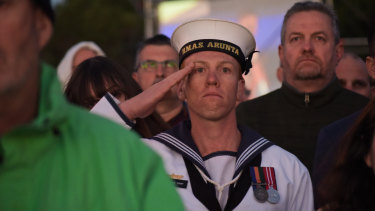 Serviceman Nick Dent salutes as the Australian national anthem is played during the ceremony.