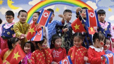 Children rehearse the welcoming ceremony with the national flags of Vietnam and North Korea.
