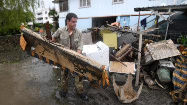 A man helps strangers remove flood-damaged items from their home in the Townsville suburb of Rosslea on Thursday.