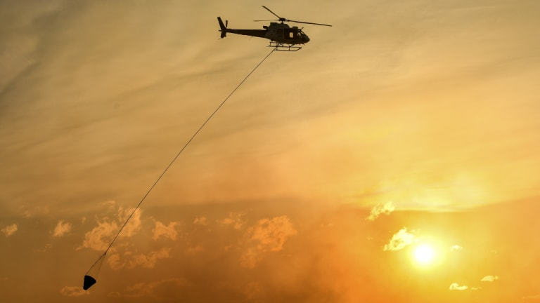 A helicopter water bombs a bushfire threatening homes in Sydney's south-west.