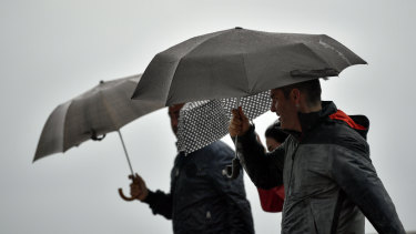 People shelter from the rain under their umbrellas, in San Sebastian, northern Spain on Sunday.