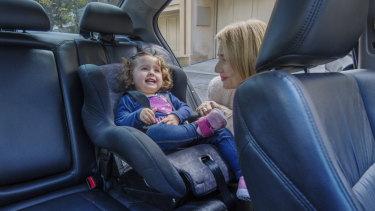 Robyn Dinh adjusting her granddaughter Audrey's car seat,