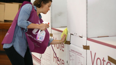Voting during COVID-19: An election official sanitising a polling booth during the Brisbane council elections in March.