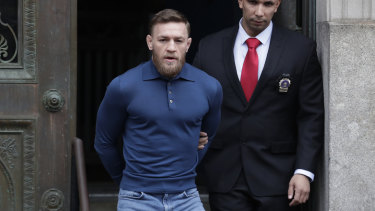 A handcuffed Conor McGregor is escourted from a New York police station on Friday after being arrested for attacking a bus of UFC rivals.