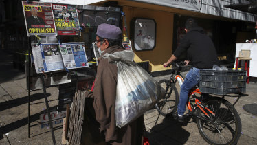 A man reads the front pages of newspapers showing the news the Mexican President Andres Manuel Lopez Obrador has COVID-19, at a kiosk on Paseo de la Reforma in Mexico City.