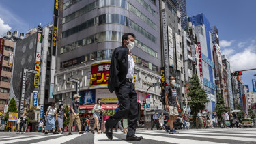 A masked-up Tokyo goes about its daily business. Community infections, unrelated to the Games, have surged.