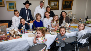 Masha Fisher surrounded by family at the table for Passover as easing health restrictions allow the Jewish gathering to occur in homes.