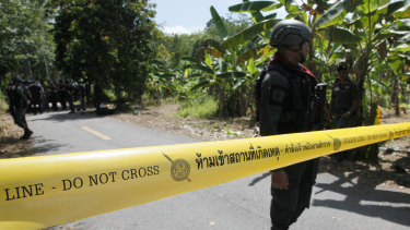Police secure the road leading to a shooting scene, in Yala province, Thailand, on Wednesday.