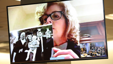 Grace's mother Gillian Millane holds a family photograph during her televised victim impact statement from her home in the UK.