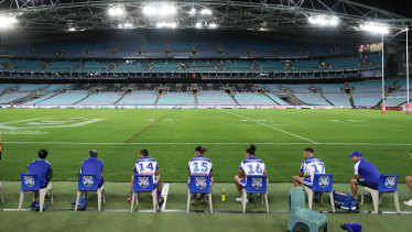 Bulldogs interchange players and support staff, seated well apart, look on at an empty ANZ Stadium in round two.