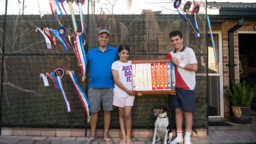 Mr Portelli with his son Eric, daughter Claire and some of his finch ribbons at his home in Sans Souci.