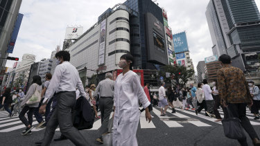 Commuters walk at Shibuya pedestrian crossings in Tokyo on Monday.