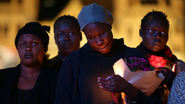 Hundreds of mourners, including Natalina Angok's sister Helena (pictured centre), have attended a vigil at Federation Square.