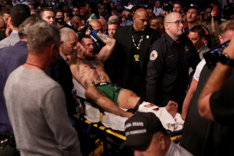 Conor McGregor is carried out of the arena after breaking his leg.