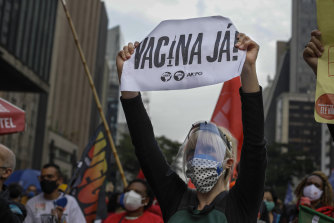 """A demonstrator holds a sign that reads in Portuguese; """"Vaccine now"""", during a protest against Brazilian President Jair Bolsonaro."""