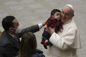 Pope Francis embraces the child of a Vatican employee in the Paul VI hall , Monday, Dec. 21, 2020.