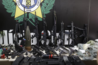 Weapons and drugs seized during a police raid are displayed for the press.