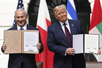 Israeli Prime Minister Benjamin Netanyahu and US President Donald Trump hold the signed documents at the White House.