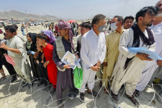 Hundreds queue outside Kabul's airport with their documents hoping to be admitted.