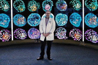 Professor Jose Polo in front of images of model embryos.