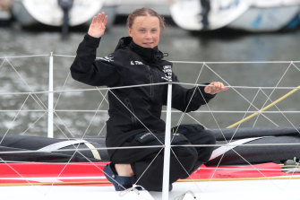 Greta Thunberg waves to her supporters on her arrival in New York aboard the zero-emissions yacht Malizia II on Wednesday.