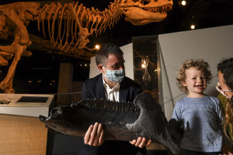 Museum Victoria Palaeontologist Dr Erich Fitzgerald shows Avery Fitzgerald, 3, from Eltham, a replica of the mandible of the recently acquired near-complete adult triceratops fossil.