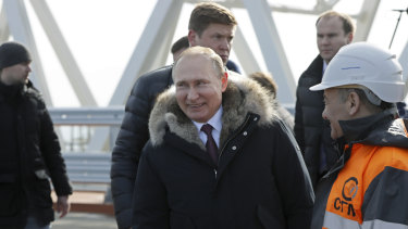 Russian President Vladimir Putin, centre, visits inspects the road section of the road-rail bridge linking Crimea to mainland Russia near Kerch, Crimea in March 2018.