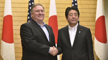 US Secretary of State Mike Pompeo, left, shakes hands with Japanese Prime Minister Shinzo Abe at the prime minister's office in Tokyo, on  Sunday.