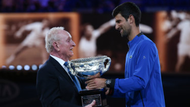 Novak Djokovic presents Laver with a trophy to mark the 50th anniversary of his second Grand Slam on January 14, 2019.