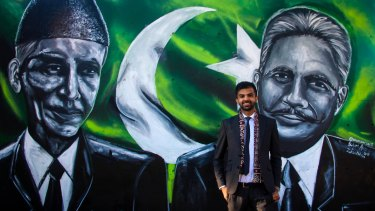 Artist Shehzar Abro alongside the mural he painted of Muhammad Ali Jinnah and Allama Iqbal on the façade of the Pakistan High Commission in Canberra.