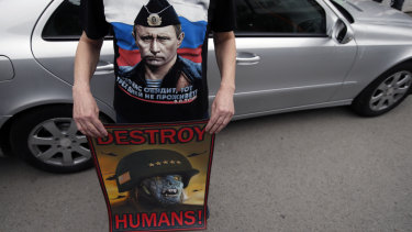 A man wearing a shirt showing a picture of Russian President Vladimir Putin holds an anti NATO poster during a protest outside the Syrian embassy in Belgrade, Serbia, on Sunday.