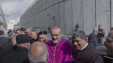 Archbishop Pierbattista Pizzaballa, the top Roman Catholic cleric in the Holy Land, center, is received by worshippers while his convoy crosses an Israeli military checkpoint from Jerusalem.