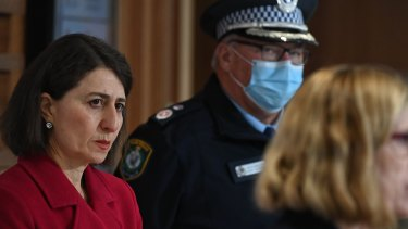 Premier Gladys Berejiklian and Deputy Commissioner Gary Worboys listen as Dr Kerry Chant delivers yesterday's COVID numbers.