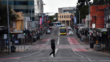 A lone person walks across Moore Street, Liverpool as Sydney bunkers down under tightened restrictions.