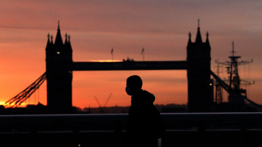 A person wearing a face mask walks across London Bridge, with Tower Bridge in the background.