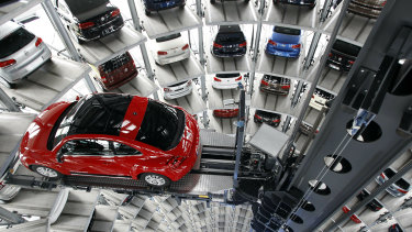 A New Beetle car is lifted inside a delivery tower after the company's annual press conference in Wolfsburg, Germany, in 2002.