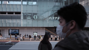 Pedestrians wearing protective masks wait for traffic lights to change near a bus terminal in the Shinjuku district of Tokyo yesterday.