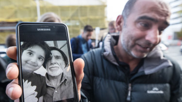Yama Nabi holds a photo of his father Haji-Daoud Nabi who was killed in the Al Noor Mosque in Christchurch.