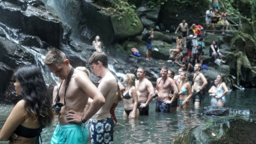 Tourists line up for photos under the Kato Lampo waterfall in Gianyar, Bali.