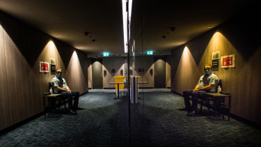 A quarantine support officer at his station near the lifts at the Four Points hotel. It is hotel ventilation systems that most worry those in the medical and occupational health fields pushing for change.