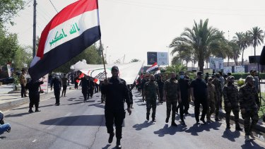 Iran-backed militia fighters march in central Baghdad, Iraq in June.