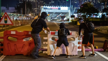People block roads during a protest against a government ban on face masks in Causeway Bay in Hong Kong, China.