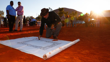 Noel Pearson signs a canvas on which the Uluru Statement from the Heart, which included the proposal for a Voice to Parliament, was later painted in May 2017.