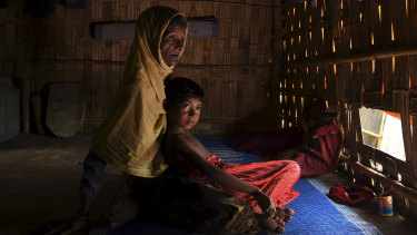 Subia Khatun, 60, holds her orphaned granddaughter Nuru Zannat aged 5 in their shelter in Kutupalong Camp, Bangladesh, in July.