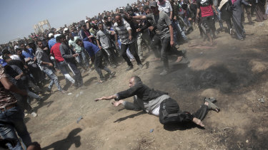 An elderly Palestinian man falls on the ground after being shot by Israeli troops.