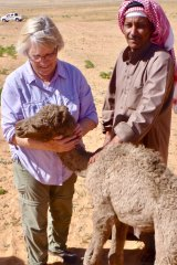Michele Cotton with a baby camel and a Bedouin client in Aqaba, Jordan.