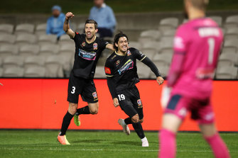 Kosta Petratos celebrates his late, late match-winner with Jets teammate Jason Hoffman as Sydney FC goalkeeper Andrew Redmayne rues an opportunity lost.