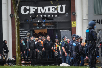 Police keep protesters away from the office of the CFMEU in Melbourne on Monday.