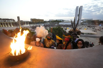 """Indigenous people stand near the """"Pyre of freedom"""" during the """"Luta pela Vida,"""" or Struggle for Life mobilization in Brasilia during a protest for Indigenous land rights."""